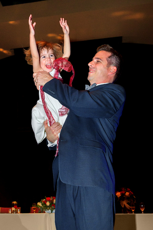 A little flower girl dances with her father at a wedding reception.  She has her hands in the air as swings her around. 版權商用圖片