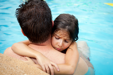 A young girl holds onto the neck of her father in a swimming pool.  She is sad and pouting.  It is a sweet, father daughter image. Stock Photo