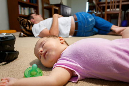 A newborn baby and her father lay sleeping on a family room floor.  The exhaustion of having a new baby has set in. Stock Photo