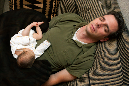 cradling: A newborn baby is curled up asleep on her sleeping father.