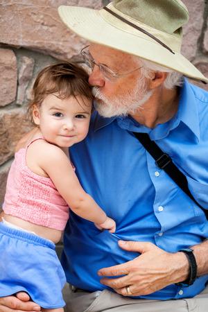 祖父は、彼女のカメラの笑ったよう頭の上彼の幼児の孫娘をキスします。 暑い日は、少し汗をかいた。
