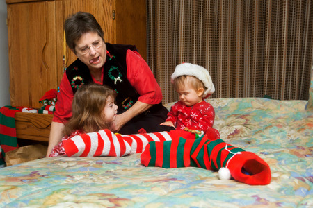 A grandmother reaches down as she strains with her tongue out to pull a Christmas stocking up, onto a bed to help her granddaughters open gifts.