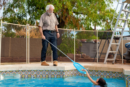 wearing slippers: A young girl in a swimming pool places leaves one by one into a skimmer net that her grandfather is holding.  He holds it patiently as she helps him.  he is wearing slippers out by the pool.
