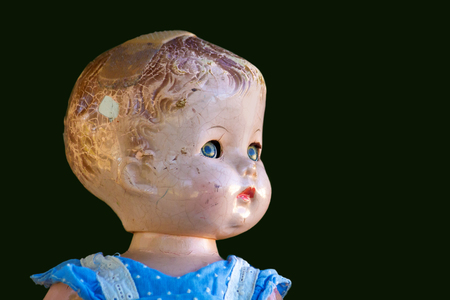 Portrait of a cracked up antique doll on green. Stock Photo