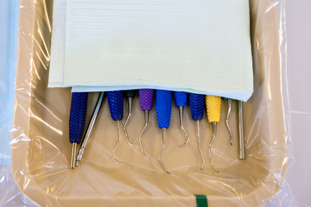 scratcher: A beige tray laid out with colorful, dental scraping tools.  They are halfway covered with a drape that will be a bib for the next patient.