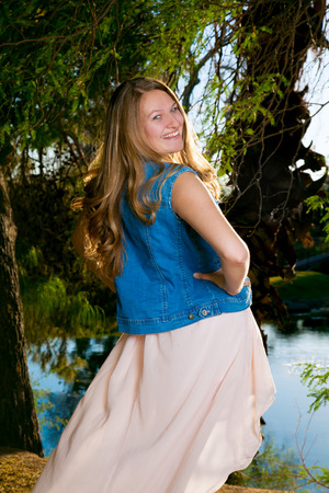 coy: A coy teenage girl tosses her hair over her shoulder as she looks back at the camera.  She is in motion and her skirt floats out behind her as her hair settles.