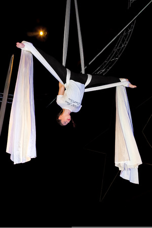 A teenage girl aerialist hangs upside down in a butterfly position before a drop. Stock Photo