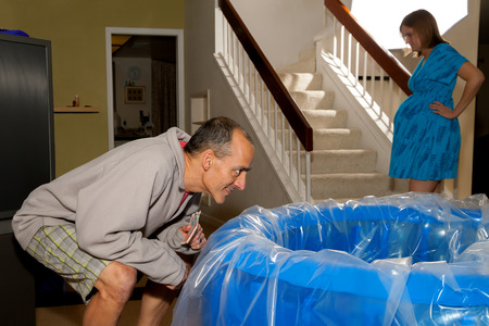 come in: A woman in labor paces in the background, preparing herself for what is to come while her husband looks eagerly at the water level in the birthing tub.  He is excited, she is anxious. Stock Photo