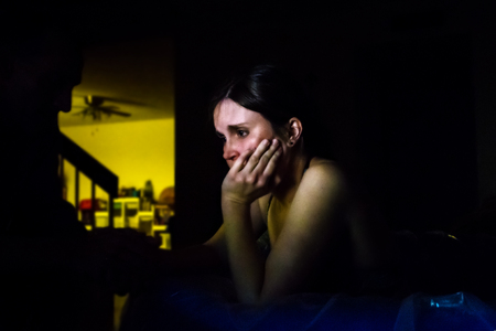 home life: A woman in labor kneels in a birthing pool in the dark.  She is holding the hand of her silhouetted husband and resting her chin in her other hand as she looks ahead with a furrowed brow.  She is worried and in pain. Stock Photo