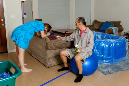 A husband sits on a birthing ball and hands his wife some vitamin C tablets as she breathes through a contraction during her home birth labor.