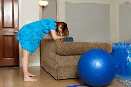 A woman in labor leans forward onto the back of a couch as she breathes through a contraction.  There is a birthing ball and a birthing tub in the room.