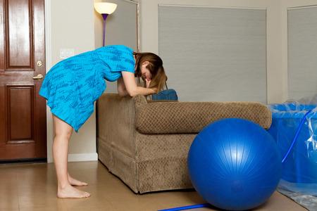 Una donna in travaglio si sporge in avanti sul retro di un divano mentre si respira attraverso una contrazione. C'è una palla parto e una vasca parto in camera. Archivio Fotografico