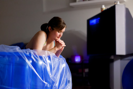contractions: A pregant woman in a birthing pool takes a quiet moment between contractions to pray.  There is an essential oil diffuser going in the background and the room is dark.