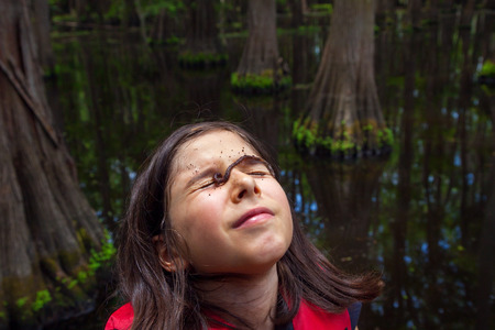 A young girl who decided to put a worm on her face before baiting her fishing hook with it.  Her face is turned up to the sun and she is squinting with a dirty worm crawling across her eyes. Standard-Bild