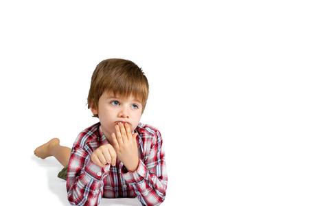 Un garçon regarde profondément dans ses pensées, allongé sur le ventre avec sa main sur ses lèvres. Ses ongles sont sales et il a l'air confus. Isolé sur blanc avec un tracé de détourage.