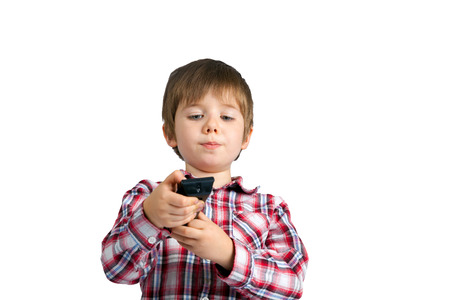 A little boy holds a remote control.  He looks like he is really focusing on which button to push.  He is holding his mouth just right.  There is a clipping path.