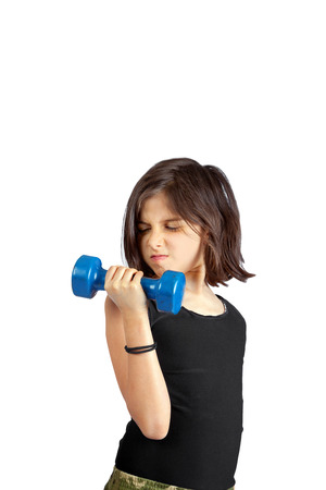 A young girl lifts a small, 5 lb dumbbell with a determined facial expression.   She is doing a bicep curl with improper form.  There are two ponytail holders on her wrist.