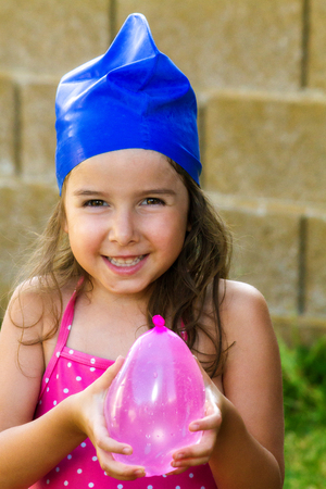 An adorable, young girl wearing a blue swim cap and holding a pink, water balloon.  She has a sweet and mischievous smile.  There is copyspace.  Fun summer image.