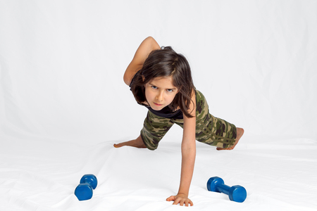 A young, brunette girl with an intense stare and camouflage pants does a one armed plank with improper form.  There are small dumbbells in front of her.  White background clipping path.
