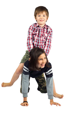 A young girl gives her little brother a horseback ride on a white background.  They are isolated with a clipping path.  Both kids are wearing camouflage pants. Banco de Imagens
