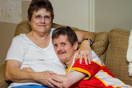 An older man with Downs Syndrome, hugs his older sister as they sit on a couch. The woman looks tired, the man looks mischeivious. He is about to tickle her.