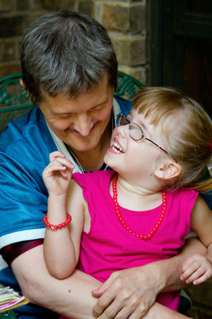 A man with Down Syndrome holds his young niece as she looks up at him, laughing.  She has thick glasses and a big smile.  He is looking down at her with a grin. Banco de Imagens
