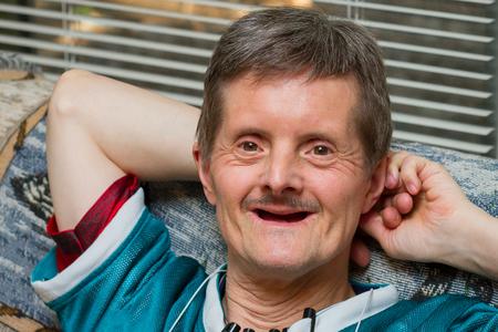 Een gelukkige man met het syndroom van Down leunt met een grote glimlach achterover op een bank. Hij is ouder en heeft al zijn tanden verloren. Hij kijkt naar de camera en heeft verschillende pennen aan zijn shirt.