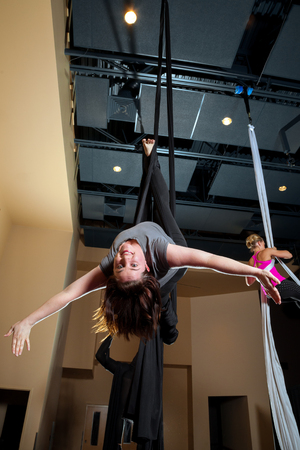 A young, adult woman performs a Rebecca Split Layout on a black, aerial silk while a classmate works on another move in the background.  The main subject is upside down and smiling.  This move takes flexibility and strength.
