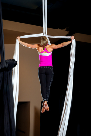 The back side of a muscular, female aerialist does a tear drop iron cross pose on a white silk.  She is very strong and the light accentuates her body structure. Banco de Imagens