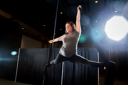 An aerialist holds onto one, black silk as she poses in a left, front split.  She is back and side lit with lots of atmospheric lens flare accenting the image.  The young woman is wearing black leggings and a grey shirt.