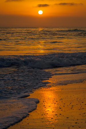 Sunset over a beach in Carlsbad, California on a slightly cloudy day.  The sky and reflection are orange as the waves wash onto the shoreline.  There are small, foamy, breaking waves in the foreground.  A distant ship floats on the horizon. Banco de Imagens