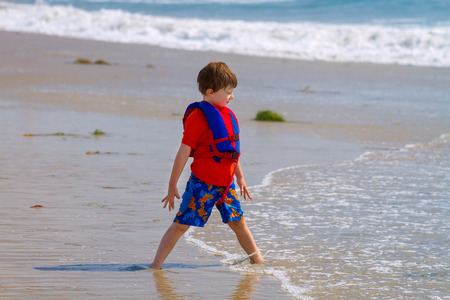 A little boy with his feet sunken into the beach sand stands with one foot in front of the other in a spread leg stance and stares out to the ocean as the water slowly comes over his ankle.  He is rooted and grounded.