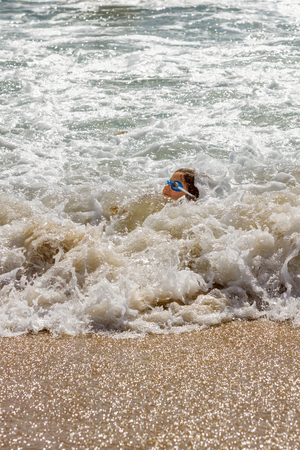 A young girl barely keeps her head above water in the foamy ocean surf on the beach.  Only the top of her head and her face show above the churning sea water.  She is wearing goggles.