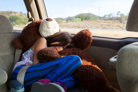 A tired little girl rides, curled up in her booster seat atop of her big, stuffed bear, in a minivan across the Southwest desert.  She looks bored and sad on her long roadtrip. Banco de Imagens