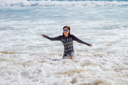A happy, young girl wearing goggles and a long sleeve bathing suit, plays in the ocean surf with a big smile.  Sea kelp floats around in the foamy water behind her.