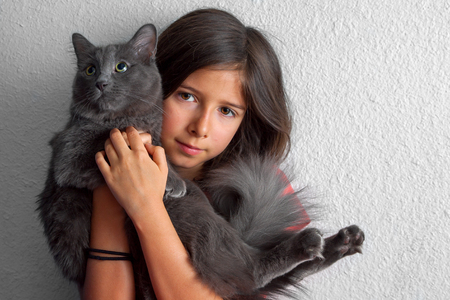 A seemingly shy, youn, brunette girl holds a fluffy grey cat close to her face.  She is looking at the camera but holding him in front of her.  He is looking up and off to the side as if he is begging.  She has ponytail holders around her wrist.  There is copy space.