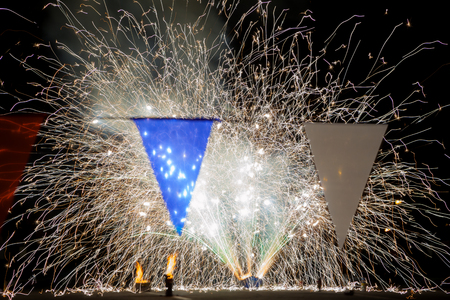 Ground level fireworks sparkling behind red, white, and blue triangular banner flags in a parking lot.  Two containers of finished fireworks are on fire. Banco de Imagens