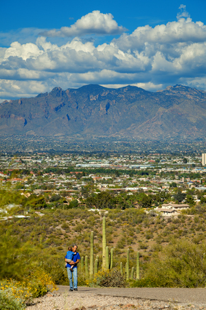 A grandfather carries his young grandson up the steep, paved path of A Mountain in Tucson, Arizona with the city in the background.  Saguaro cacti behind them with of view of the Catalinas. Banco de Imagens