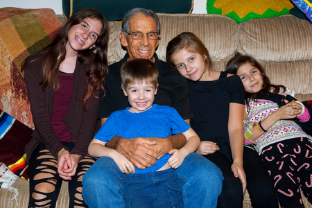 A happy grandfather sits on a mismatched couch with four of his grandchildren, three granddaughters and a grandson. Banco de Imagens