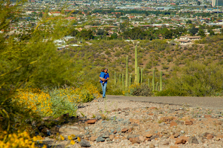 A grandfather carries his young grandson up the paved path of A Mountain in Tucson, Arizona.  The desert is blooming and there is a lot of green in the brush, including saguaros and the city in the background.