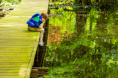 An impatient young, fishing boy stares at his still bobber, willing it to move, as he leans over the edge of the dock he is fishing from at Lake Bistineau, Louisiana.  He is wearing a life jacket.