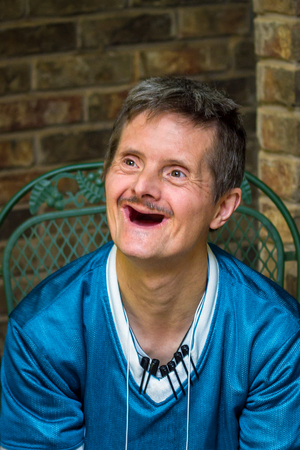 An older man with Downs Syndrome gives a huge smile.  The delight on his face shows off the fact that he has no more teeth.  The markers clipped to his shirt show that he collects pens. Banco de Imagens