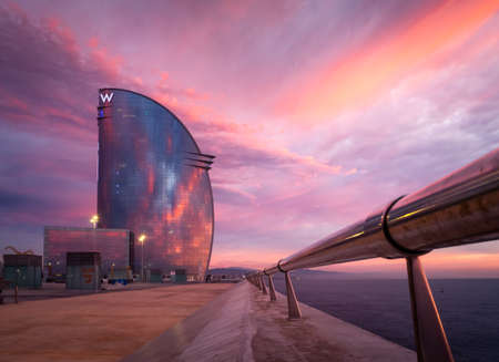 Barcelona, Spain - Februari 11 2020: The W Barcelona Hotel during sunrise, is located in the Barceloneta district of Barcelona, in the expansion of the Port of Barcelona. Publikacyjne
