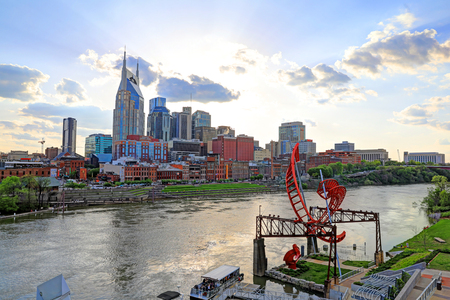 Nashville, Tennessee, USA - April 27, 2018: Downtown Nashville, Tennessee, The Music City, seen at dusk from The Cumberland River. Редакционное