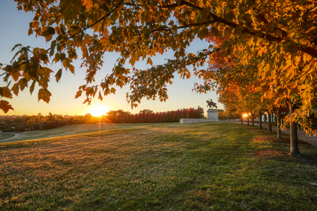 October 20, 2018 - St. Louis, Missouri - The sunrise and fall foliage around the Apotheosis of St. Louis statue of King Louis IX of France on Art Hill in Forest Park, St. Louis, Missouri. 版權商用圖片