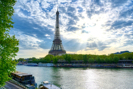 The Eiffel Tower across the Seine River in Paris, France on a sunny day with beautiful clouds.