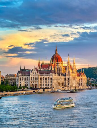The Hungarian Parliament Building located on the Danube River in Budapest Hungary at sunset.