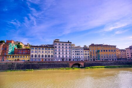 A daytime view along the Arno River in Florence, Italy.