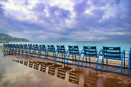 Blue chairs along the Promenade des Anglais on the Mediterranean Sea at Nice, France along the French Riviera.