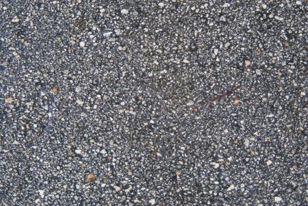 Wet street asphalt with rocks and rough texture photo